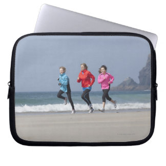 Family running together on beach laptop sleeve