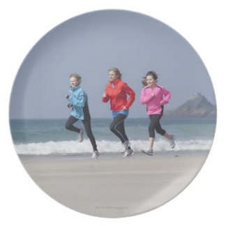 Family running together on beach plate