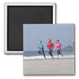 Family running together on beach square magnet