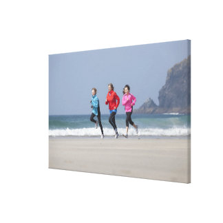 Family running together on beach stretched canvas prints