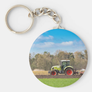 Farmer on tractor plowing sandy soil in spring basic round button key ring