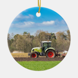 Farmer on tractor plowing sandy soil in spring christmas ornament