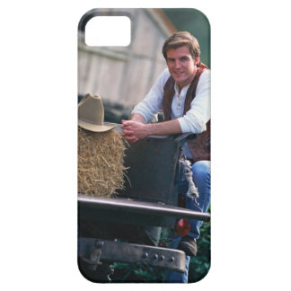 Farmer posing by pickup truck with hay bale iPhone 5 covers