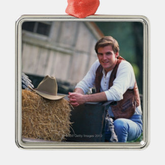 Farmer posing by pickup truck with hay bale christmas ornament