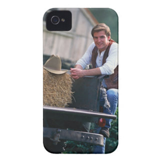 Farmer posing by pickup truck with hay bale iPhone 4 Case-Mate cases
