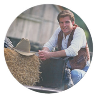 Farmer posing by pickup truck with hay bale plate