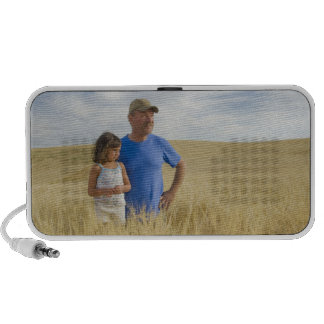 Farmer with a 5 year old girl in a field of travel speakers