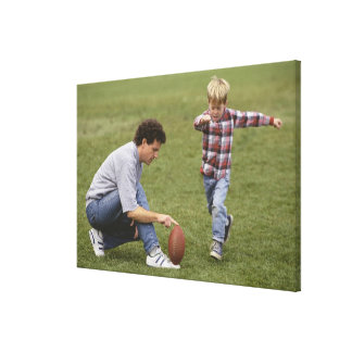 Father and son (4-6) playing American football Canvas Print