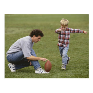 Father and son (4-6) playing American football Postcard
