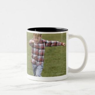 Father and son (4-6) playing American football Two-Tone Coffee Mug