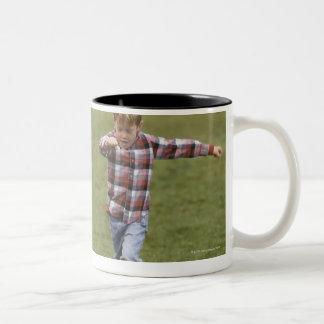 Father and son (4-6) playing American football Two-Tone Coffee Mug