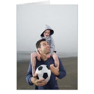 Father carrying son on shoulders and holding greeting card
