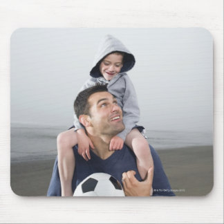 Father carrying son on shoulders and holding mouse mat