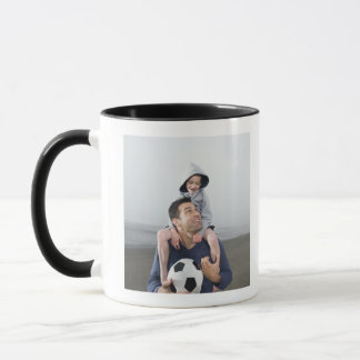 Father carrying son on shoulders and holding mug