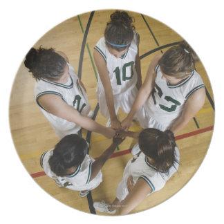 Female basketball team having group handshake, plate