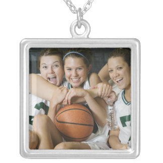 Female basketball team smiling, portrait silver plated necklace