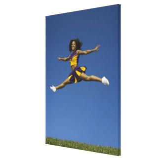 Female cheerleader doing jump splits in air canvas print