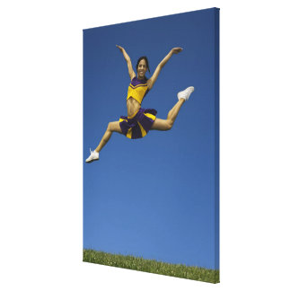 Female cheerleader jumping in air, arms canvas print