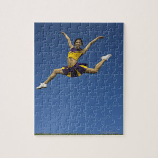 Female cheerleader jumping in air, arms jigsaw puzzle
