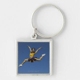 Female cheerleader jumping in air, arms key ring