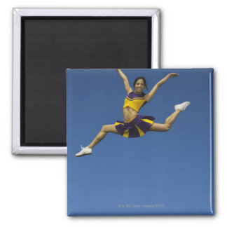 Female cheerleader jumping in air, arms magnet