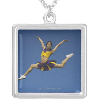 Female cheerleader jumping in air, arms silver plated necklace