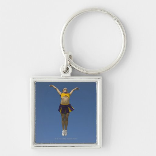 Female cheerleader jumping in air, front view key chains
