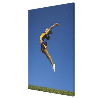 Female cheerleader jumping in air, side view canvas print