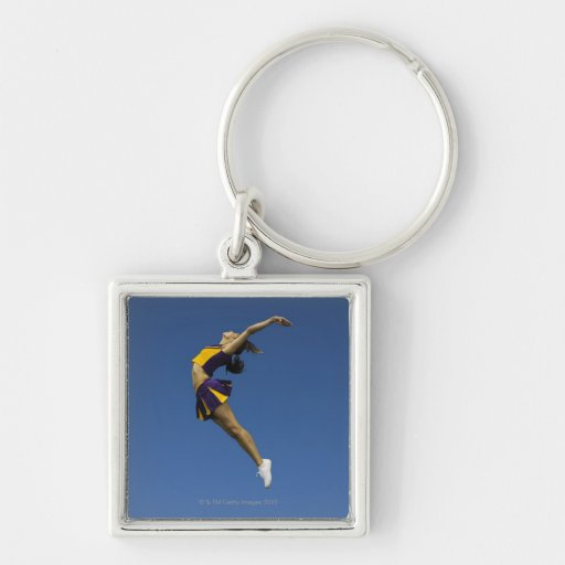 Female cheerleader jumping in air, side view key chain