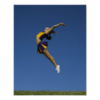 Female cheerleader jumping in air, side view poster