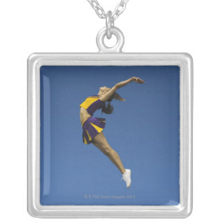 Female cheerleader jumping in air, side view silver plated necklace