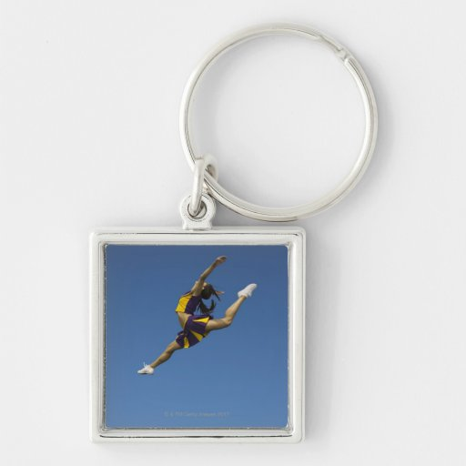 Female cheerleader leaping high up in air key chains
