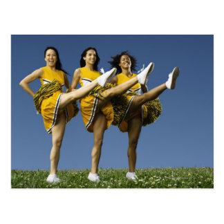 Female cheerleaders doing high kicks postcard