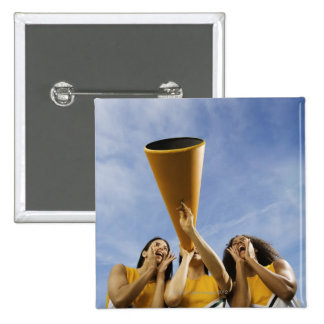 Female cheerleaders shouting through megaphone, 15 cm square badge