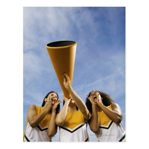 Female cheerleaders shouting through megaphone, postcards