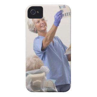 Female dental hygienist examining an X-Ray iPhone 4 Case-Mate Cases
