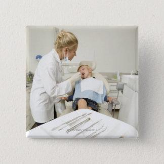Female dentist examining little boy 15 cm square badge