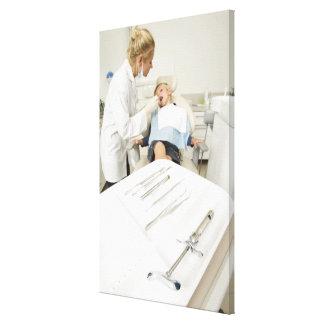 Female dentist examining little boy canvas print