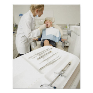 Female dentist examining little boy poster
