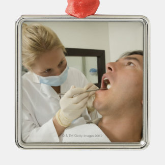 Female dentist examining man christmas ornament