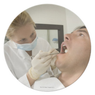 Female dentist examining man plate