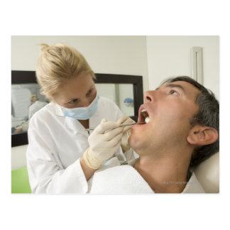 Female dentist examining man postcards