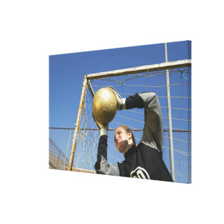 Female goalie (12-14) holding ball, low angle canvas print