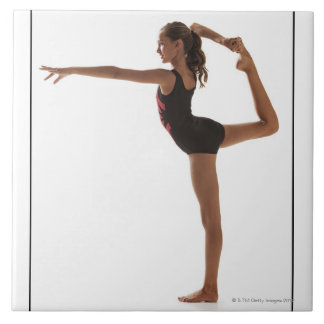 Female gymnast (12-13) balancing on one leg tile