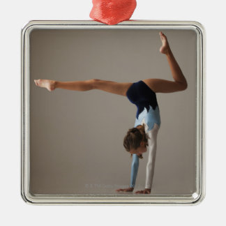 Female gymnast (12-13) performing handstand christmas ornament