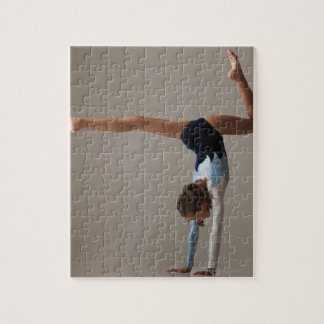Female gymnast (12-13) performing handstand jigsaw puzzle