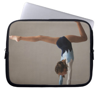 Female gymnast (12-13) performing handstand laptop sleeve