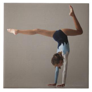 Female gymnast (12-13) performing handstand tile