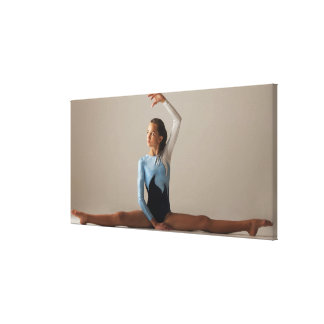 Female gymnast (12-13) performing splits canvas print