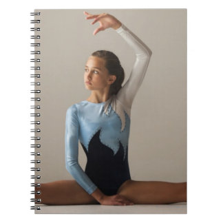 Female gymnast (12-13) performing splits notebook